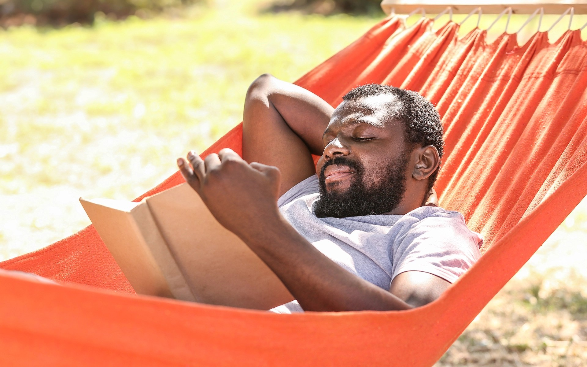 6 Books to Add to Your Summer Reading List - A man reading a book in a hammock