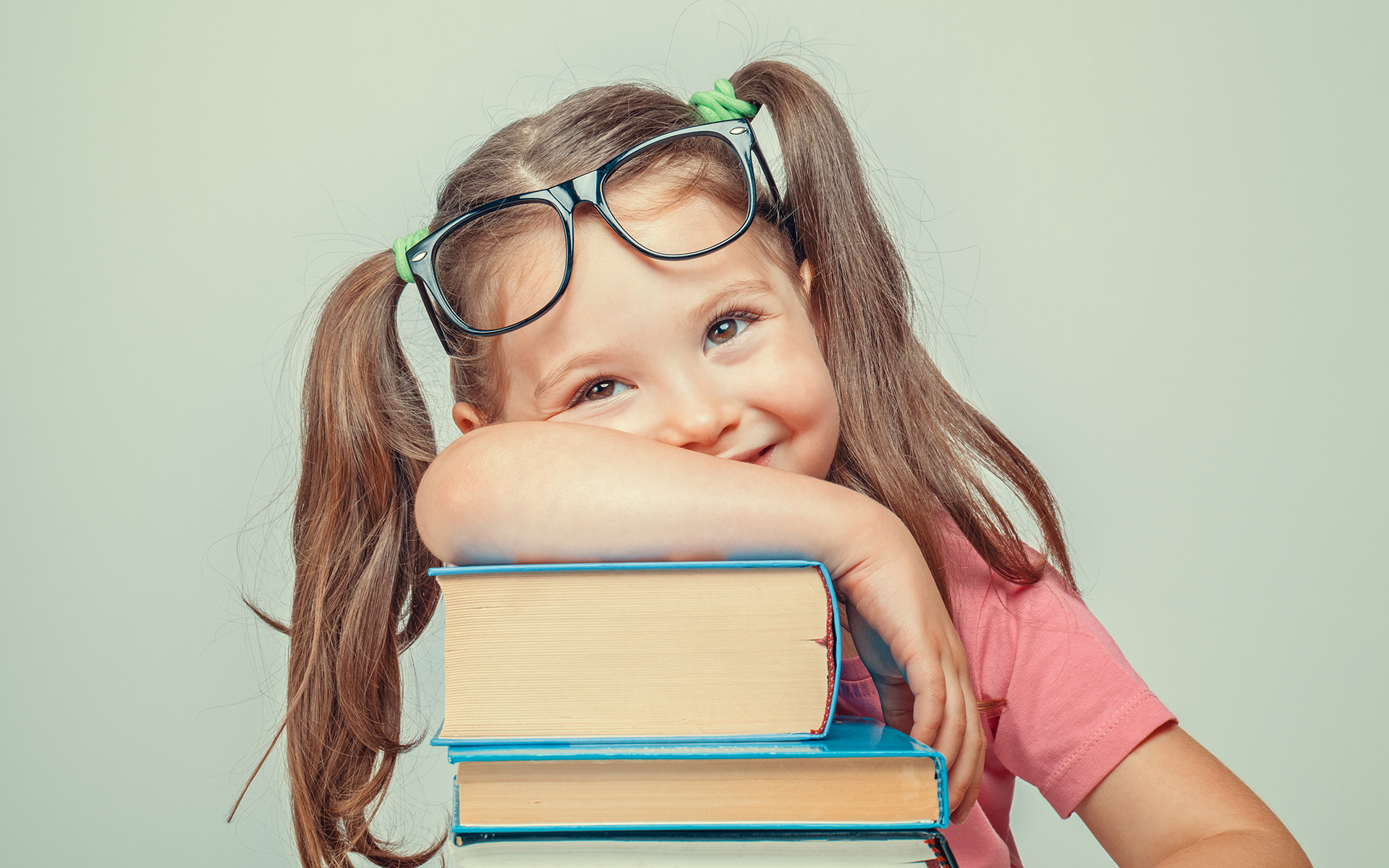 7 Classic Children's Books that Teach Kids Mindfulness -Smiling beautiful cute little girl leaning on thick books