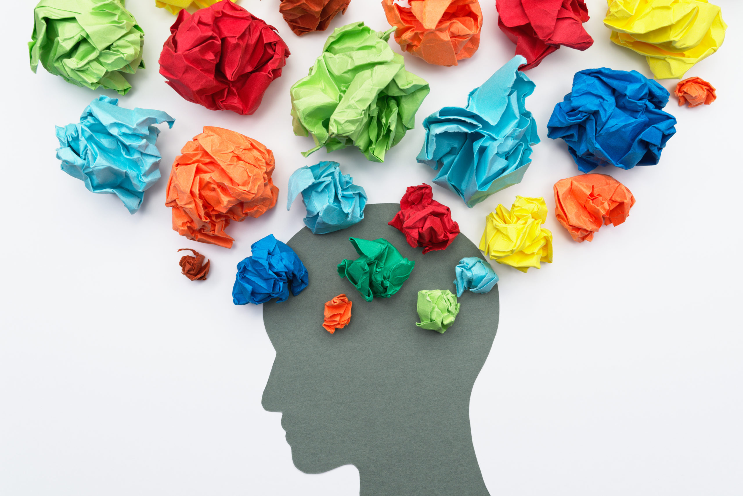 This is your brain on lies - Crumpled pieces of colorful paper arranged around the image of a head to represent thoughts