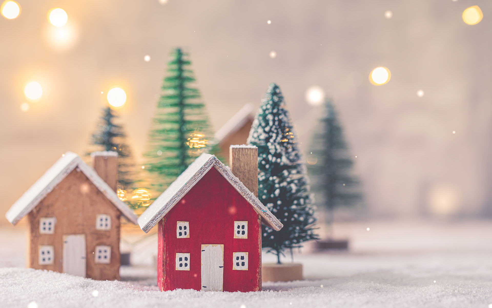 Home for the Holidays: A Self-Love Practice -Miniature wooden houses on the snow over blurred Christmas decoration background, toned, postcard concept
