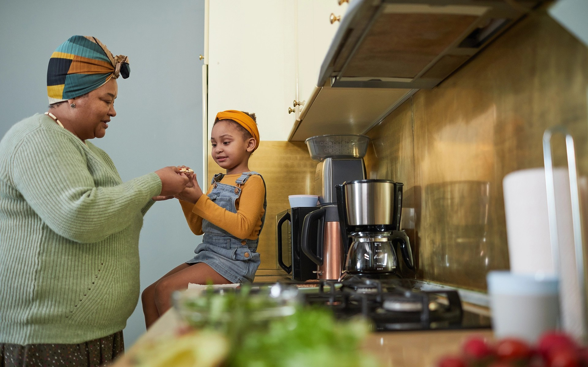 Side view portrait of cute African-American girl sitting on kitchen counter and enjoying healthy snack with grandmother in cozy home interior, copy space