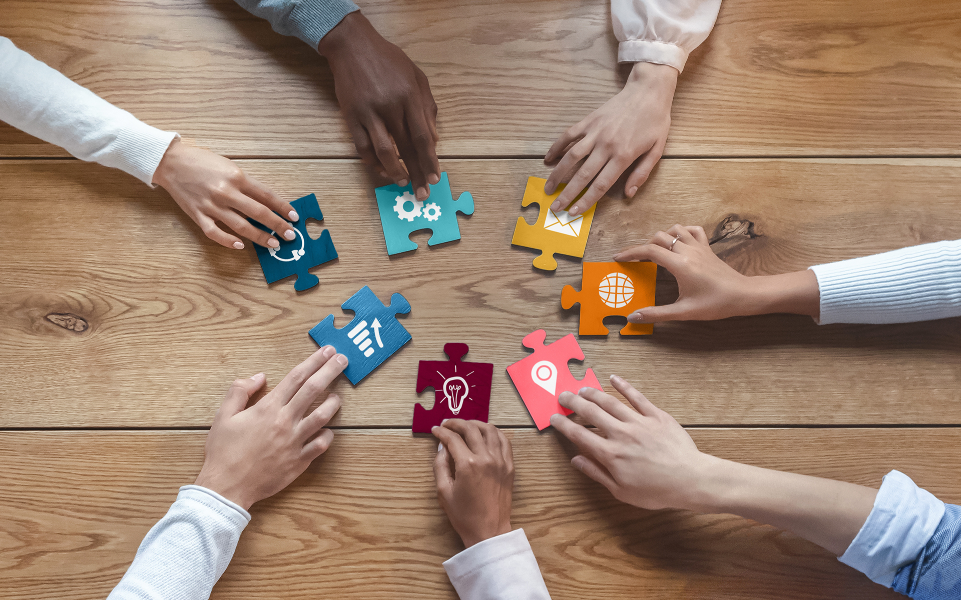 IBme Turns Toward Collaborative Leadership - Hands of international coworkers putting colorful puzzles together
