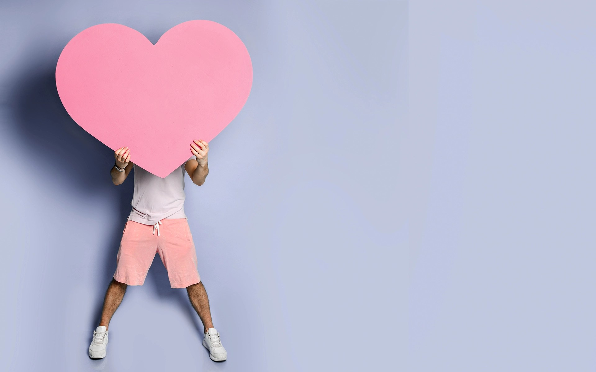 Loving-Kindness Guided Meditation - Young man hide his face behind pink heart shape toy in hands on