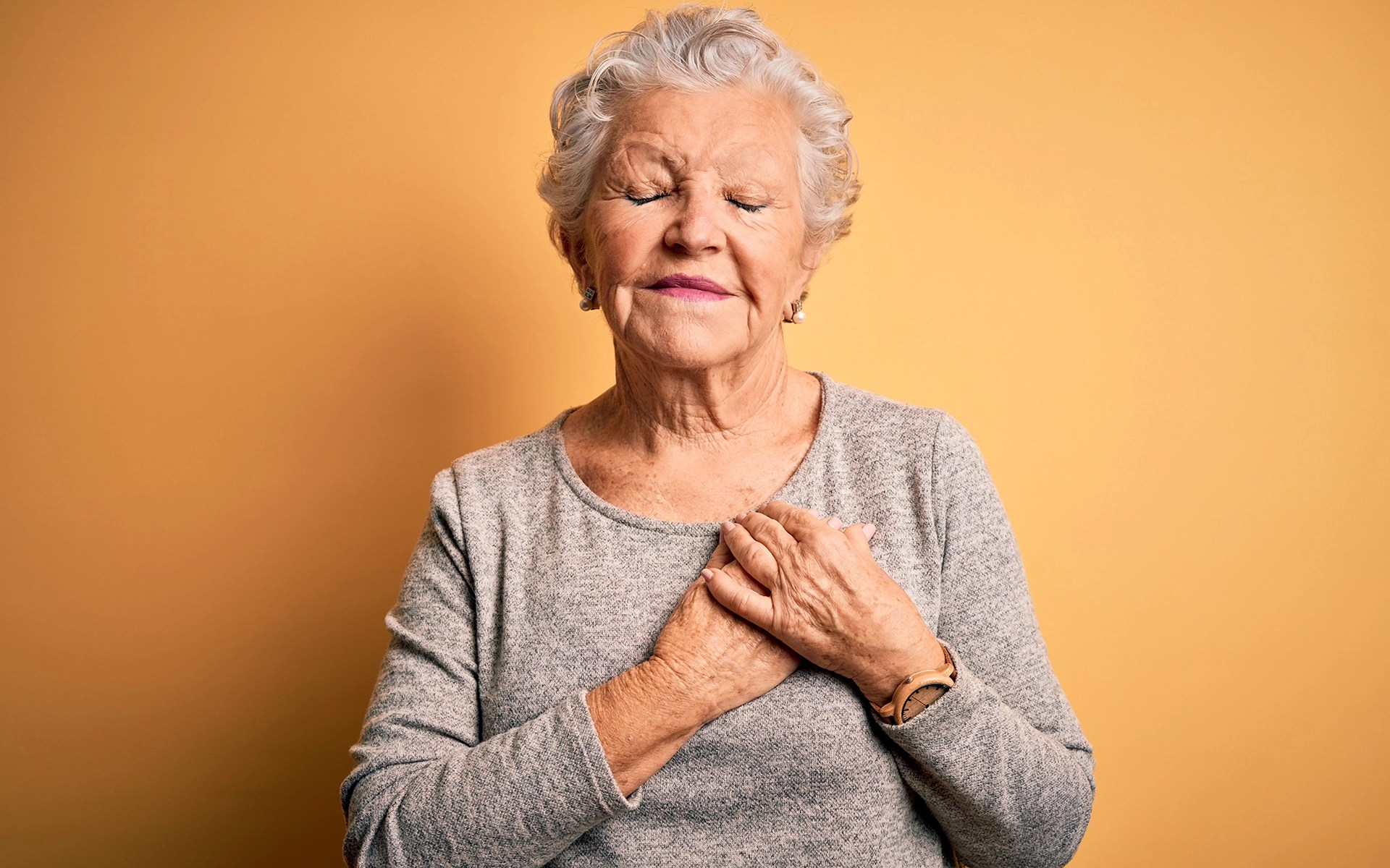 Senior beautiful woman wearing casual t-shirt standing over isolated yellow background smiling with hands on chest with closed eyes and grateful gesture on face.