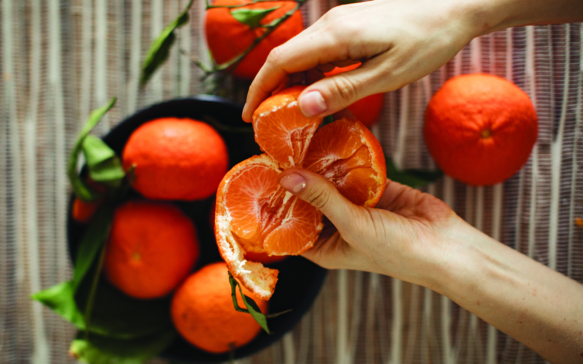 The BASICS of Mindful Eating—Photo of someone peeling clementines over a bowl of un-peeled clementines.
