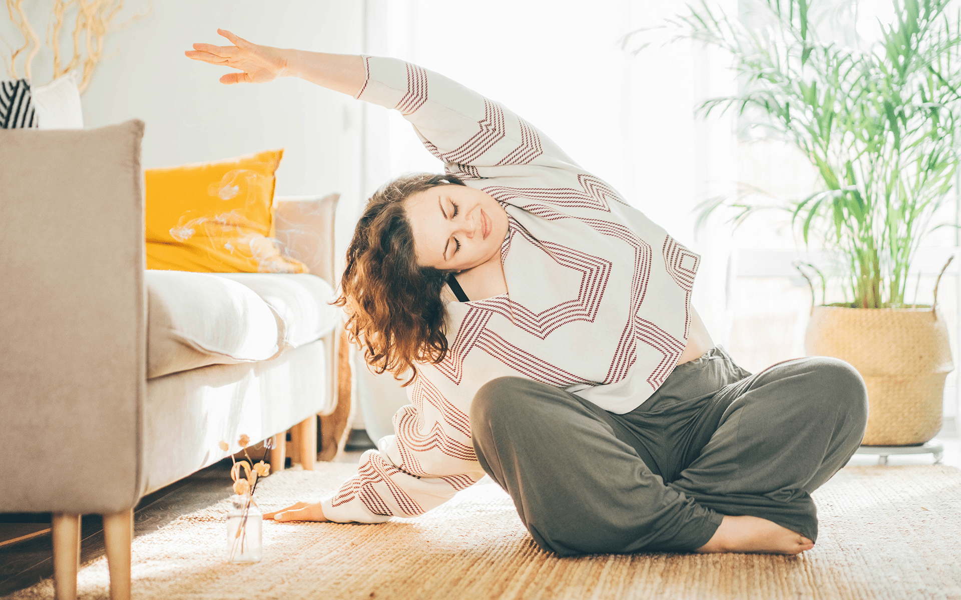 Using the Body and Breath to Get Out of Your Head—A white woman sits cross-legged on the floor of her light-colored living room and stretches one arm over her head to the left. She's wearing green pants and a beige and white sweater.