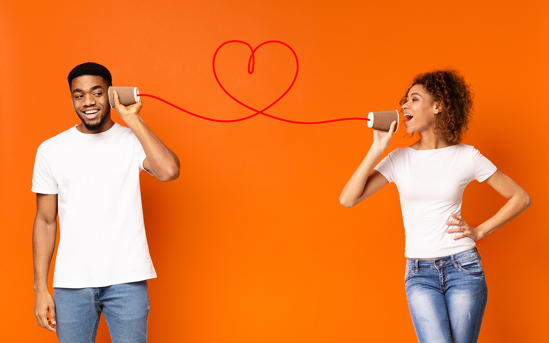 What Does Connection Mean to You? - Smiling man listening to his girlfriend through can phone, orange studio background