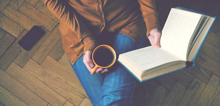 woman reading book with coffee
