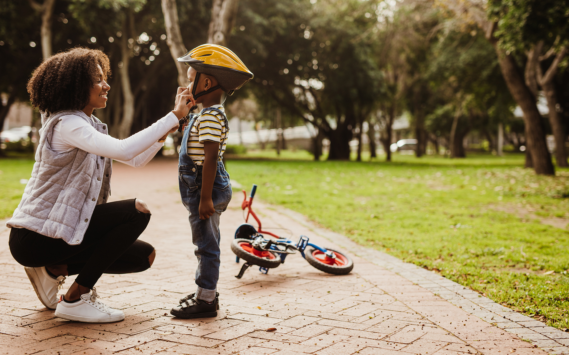 Cultivating courage and confidence in motherhood - Mother helping son wearing helmet for cycling