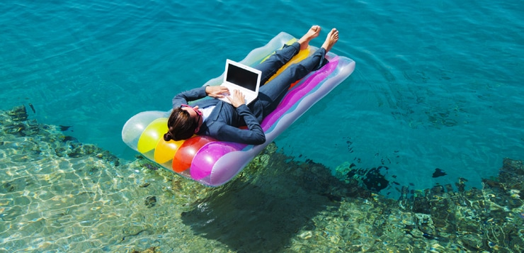 woman on floating mattress with laptop on ocean
