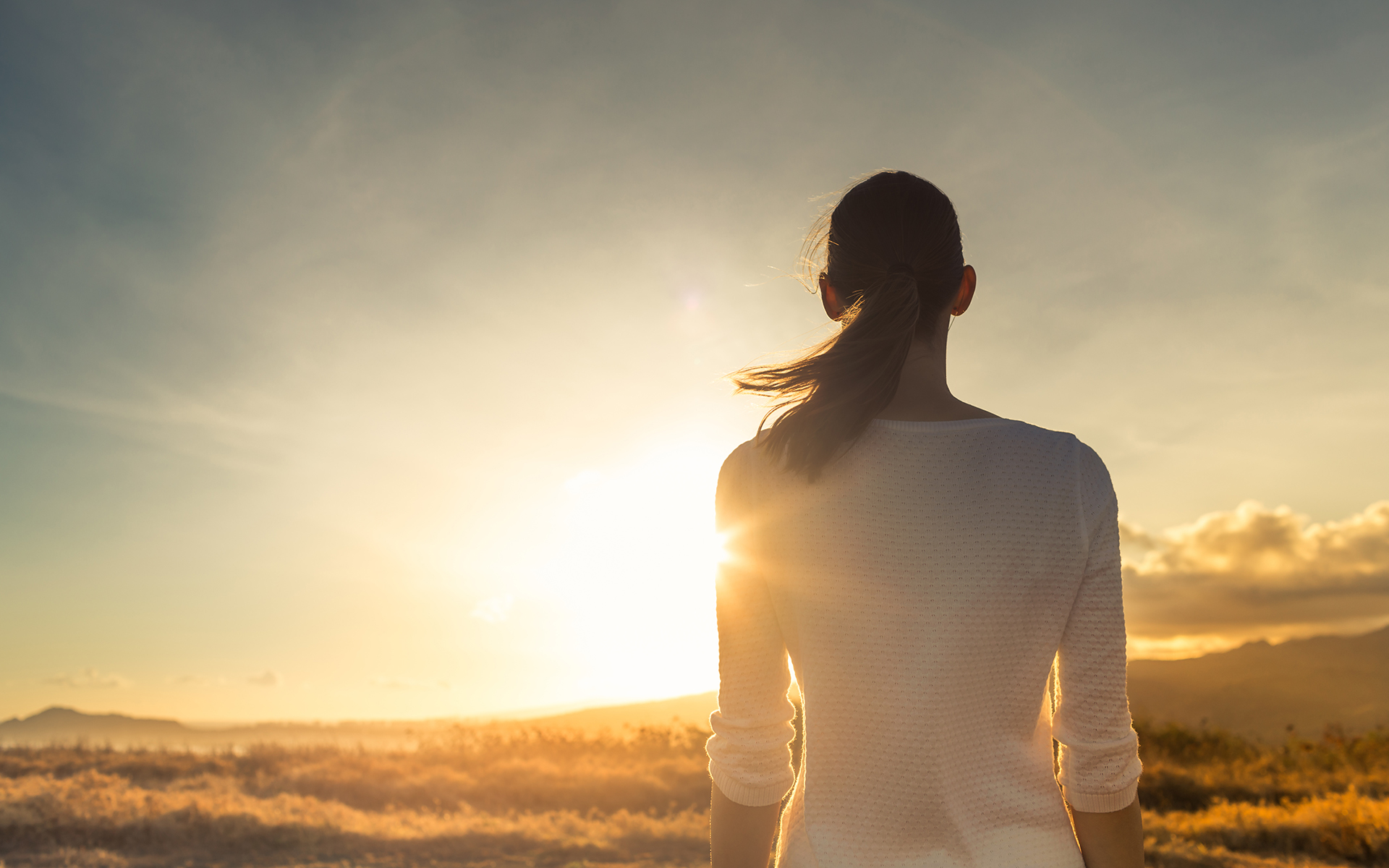 How to avoid feeling overwhelmed in stressful times - Woman admiring a sunset