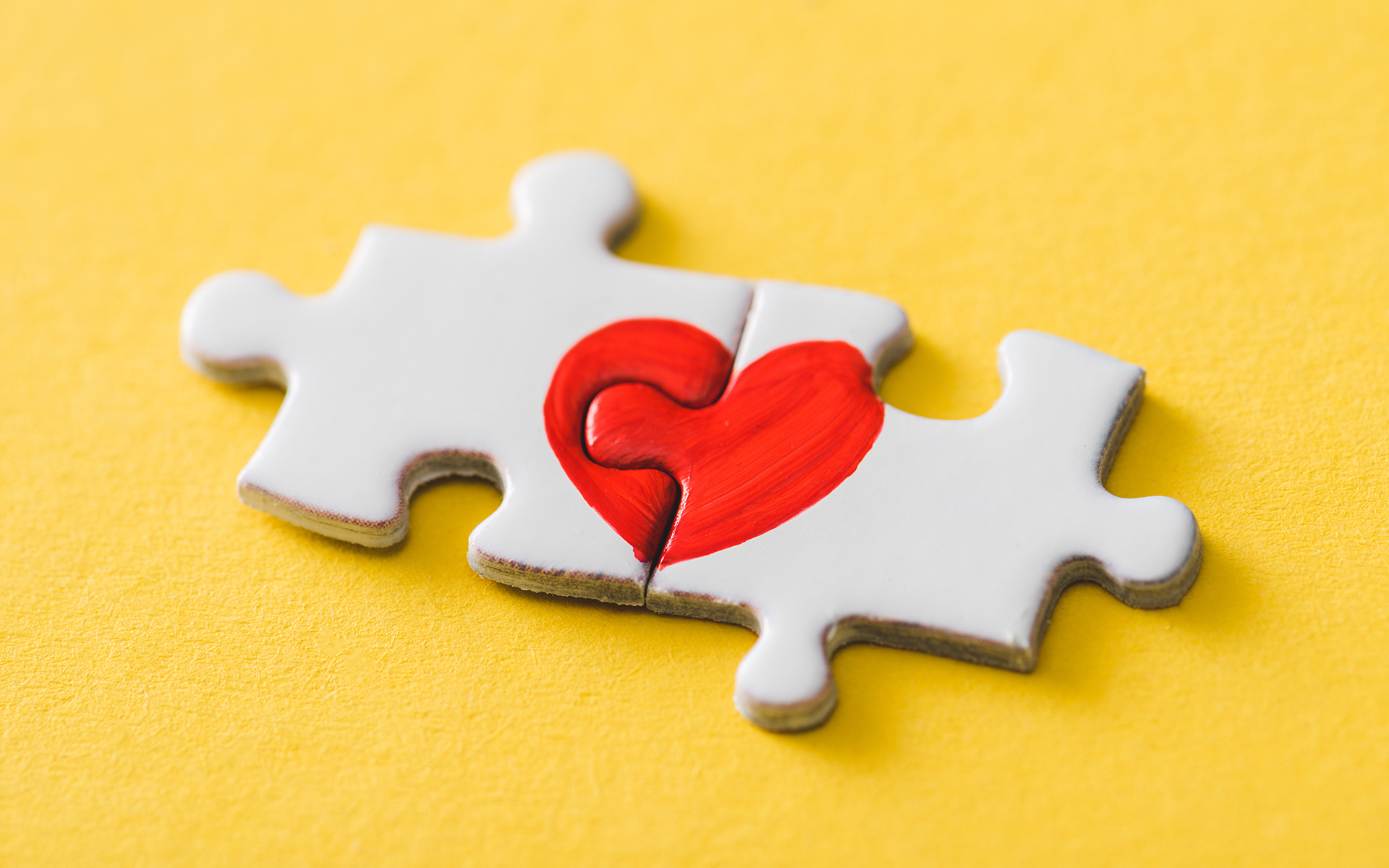 How to Deepen Empathy and Reconnect with Your Estranged Child - connected puzzle pieces with drawn red heart on yellow