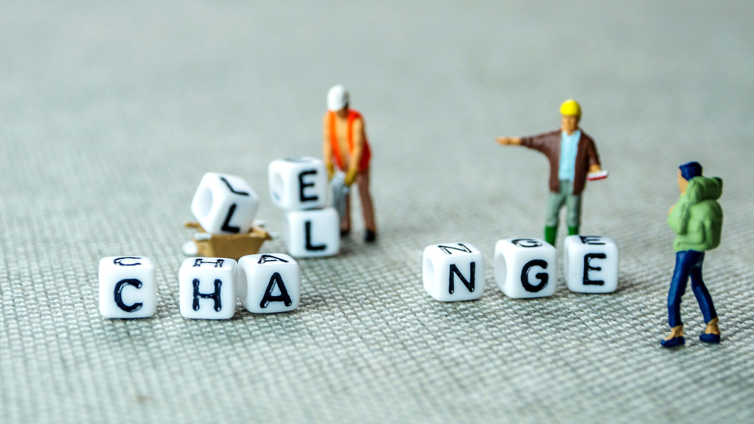 How Resilient Leaders Adapt to Change - Photo of three tiny figurines beside white blocks with letters on them. The figures are removing three letters from the word