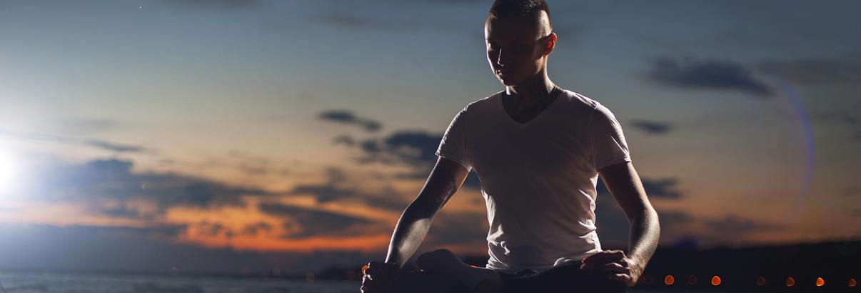 man meditating outdoors at sunset