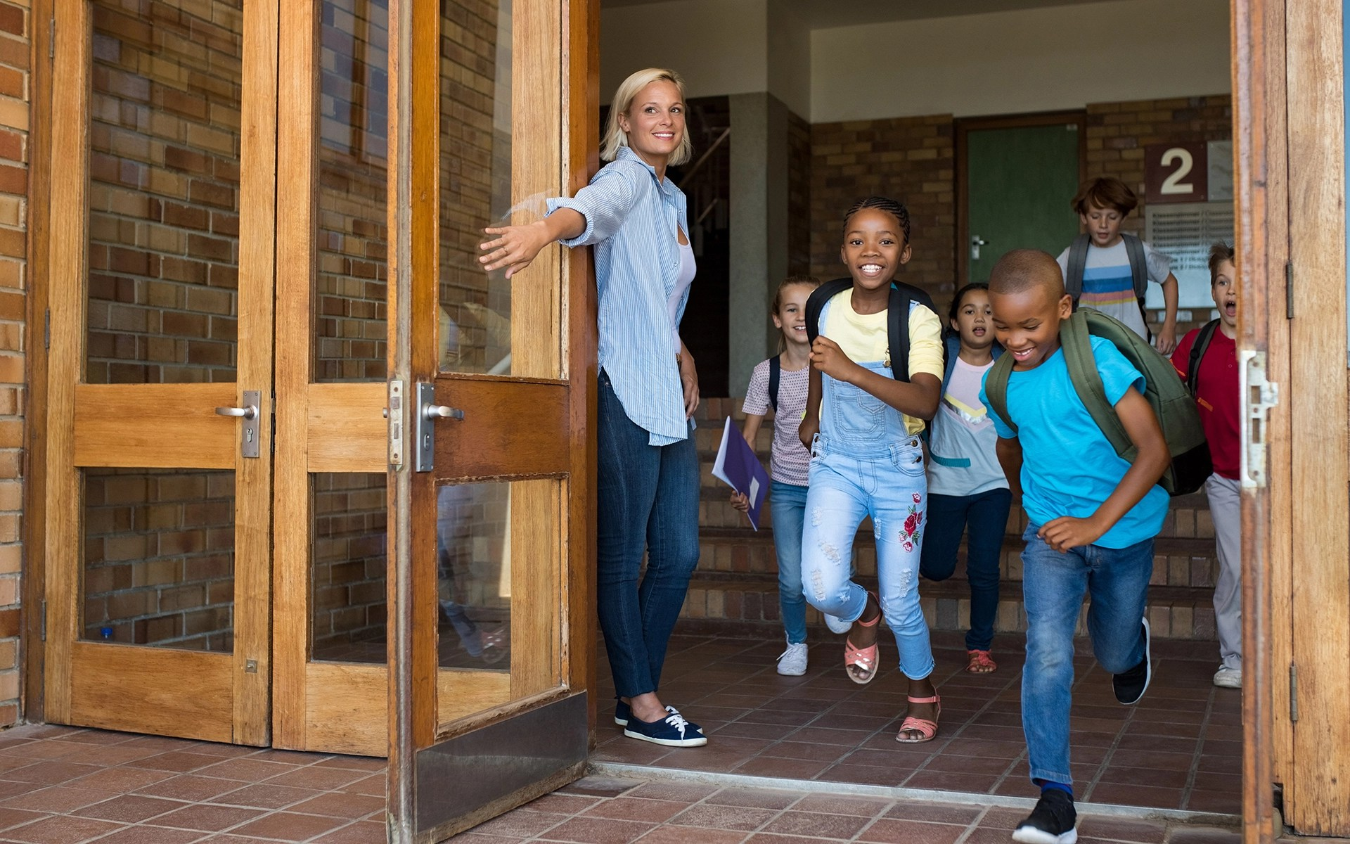 What Mindfulness Brings to an Elementary School Classroom - A teacher holds a classroom door open for students running outside