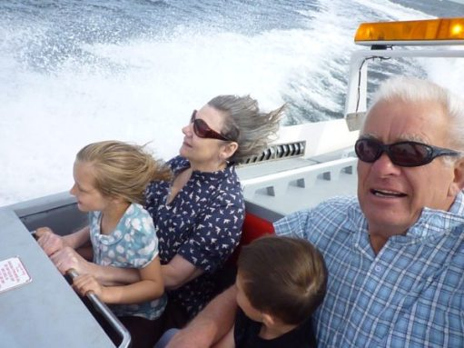 Bobby & Diddley on a speedboat ride. Each has a grandchild on their lap.