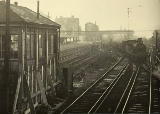 "The Footbridge: 1928 looking north before Wimbledon Station was completely rebuilt. The ""milk dock"" is middle distance, behind the signal box in the foreground."