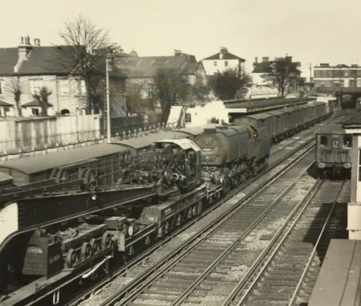 """The Footbridge: 1957, during Bobby's train spotting days. A Q1 freight engine pulling a large crane and just about to pass the freight vans in the """"Milk Dock""""."""