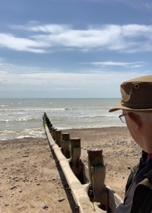 Bobby sat on a groyne on Ferring Beach looking out to the horizon over the sea.