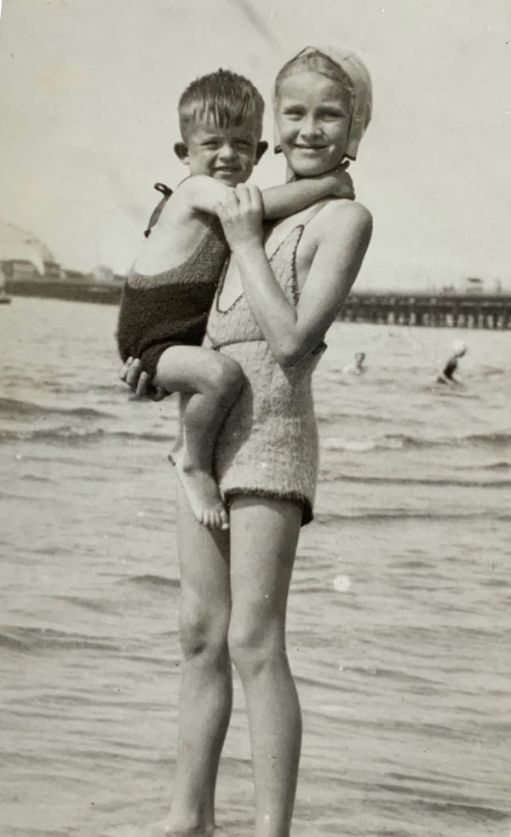 Bobby in his sister Wendy's arms. She is standing on the edge of the water, with what looks like Ryde Pier in the background.