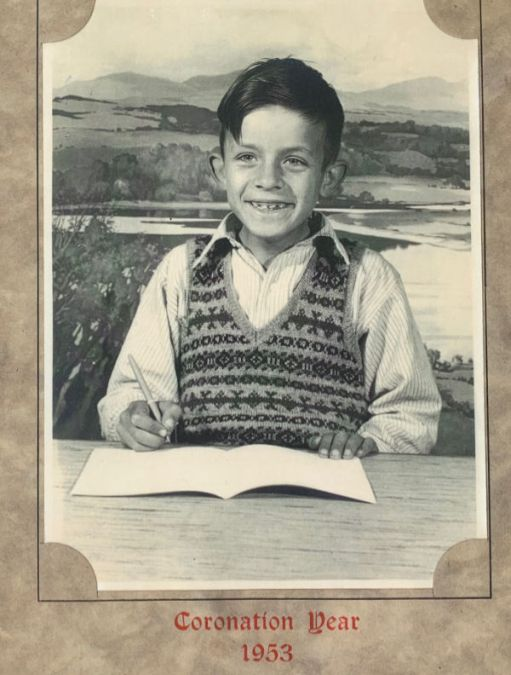 Bobby posing for a photograph at a desk with an open excercise book and pen in his right hand. He is wearing a Fair Isle jumper knitted by his Mum. The photo is in a frame , captioned Coronation Year 1953.