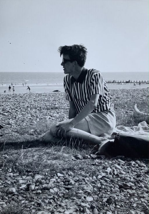 Bobby sat on a pebble beach. He is looking over the expanse of pebbles towards people playing in the sea. There is some grass growing through where he is sat.
