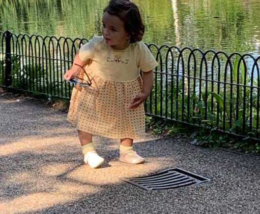 Picture of a young girl, holding a pair of glasses in her right hand, looking at a drain cover in the path.