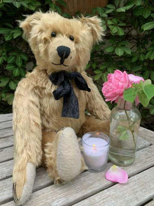 Bertie sat on an outdoor wooden table, along with a pink rose in a bottle and a lit candle in a glass.