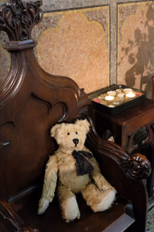 Bertie in a chair by a tray of lit candles, one of which is for Diddley.