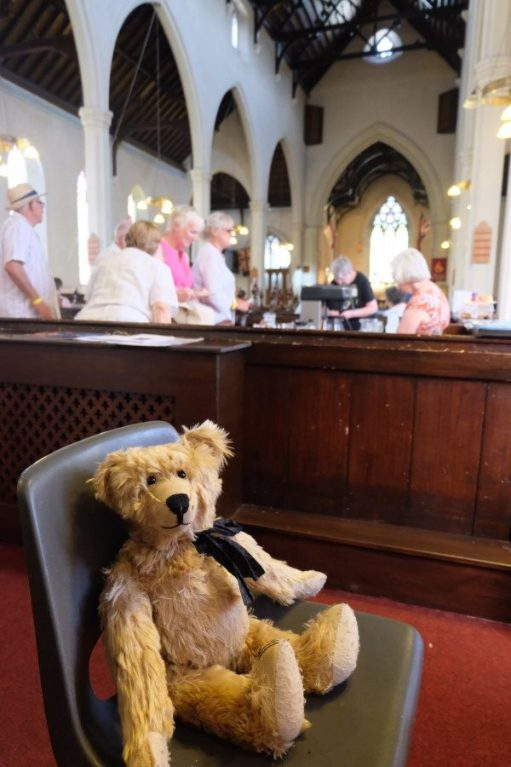 Bertie sat in a chair in the Nave, with tea and cake being served behind.