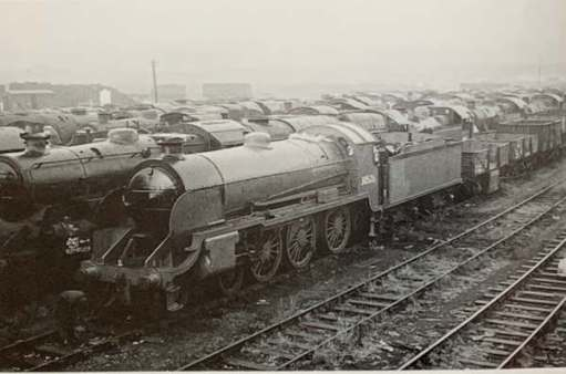 30506 amongst a line a locomotives, along with some trucks, awaiting scrap or salvage.