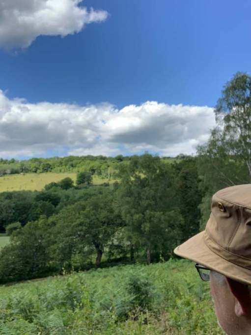 Shot looking over Bobby's shoulder showing mainly his hat and his glasses as he enjoys the view over Abinger Roughs.