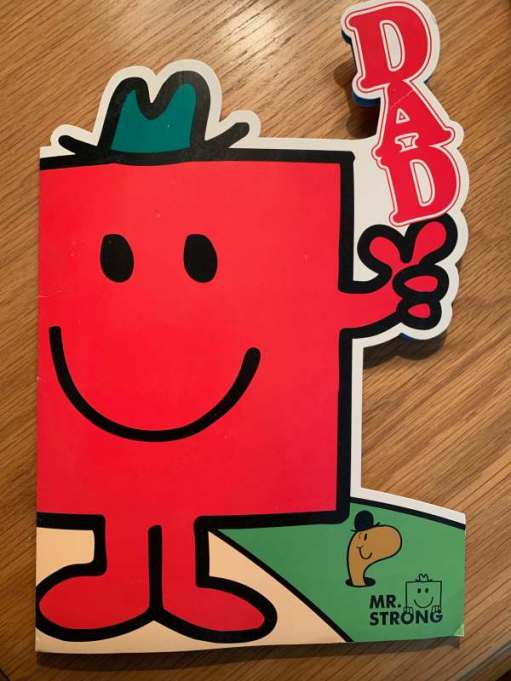 "A ""Mr Men"" card. Mr Strong, with the word ""DAD"" standing vertically on his left hand. The card is cut around around the general shape."