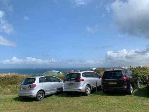 Three cars parked on grass overlooking the Pembrokeshire coastline.
