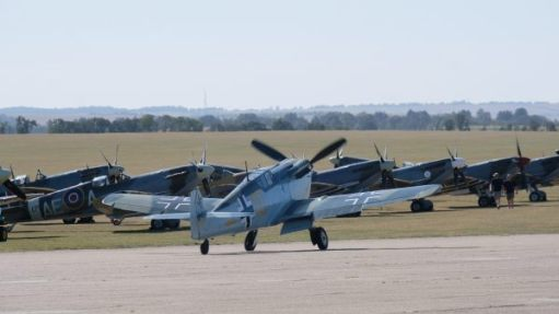 Messerschmitt 109 taxiing along the runway in front of parked Spitfires at Duxford 2019.