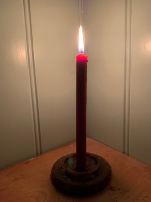 A lit candle on a table in a corner. For Diddly and the Haemophilia Society.