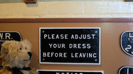 "Somerset & Dorset Railway Museum: Bertie in front of a sign in the Gentlemen's toilet that reads ""Please adjust your dress before leaving""."