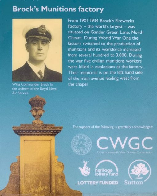 """Notice explaining the memorial: """"Brock's (sic) Munitions Factory. From 1901 to 1934 Brock's (sic) Firework Factory - the world's largest - was situated on Gander Green Lane, North Cheam. During World War One the factory switched to the production of munitions and its workforce increased from severl hundred to 3,000. During the war five civilian munitions workers were killed in explosions in the factory. Their memorial in on the left hand side of the main avenue leading west from the chapel."""" There is a photograph of Wing Commander Brock in uniform. The sign was placed by Surrey County Council."""