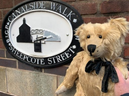 "Close-up of Bertie and the ""Canalside Walk Sheepcote Street"" sign."
