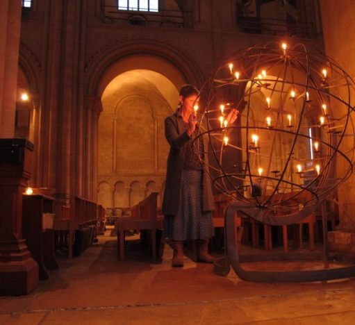 Diddley lighting a candle in an open wire globe inside a church.