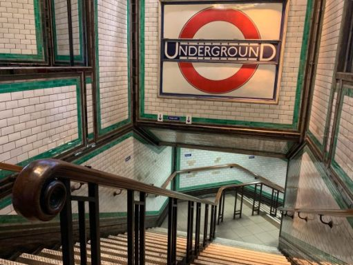 Close-up of the staircase and central mahogony handrail. The large, tiled Underground roundel looks over the scene.