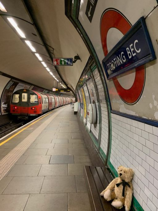Bertie sat on a bench at Tooting Bec Station. A roundel is above the bench. A train is departing, away from the camera, heading to Morden.