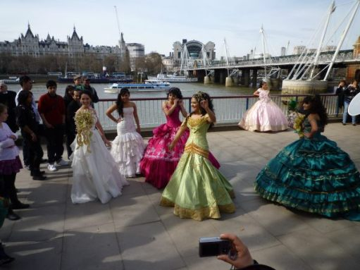 Lots of young ladies dancing on the promenade alongside the Thames. They are all in long, flowing dresses.