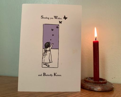 "Lighting a Candle for Diddley. A card with ""Sending you Wishes and Butterfly Kisses"" written on it, alongside a lit candle."
