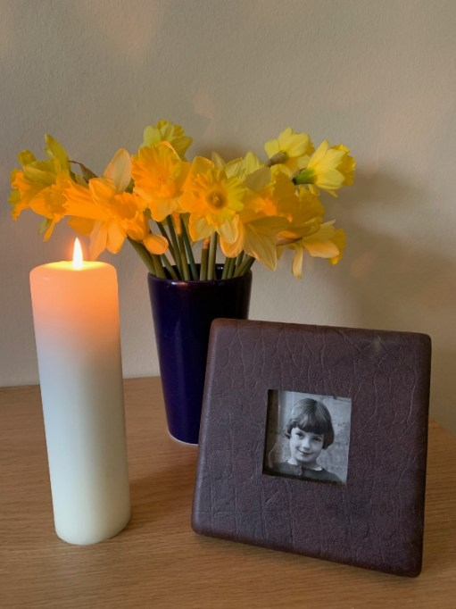 A lit candle, a bunch of daffodils in a vase alongside a picture of a young Diddley.