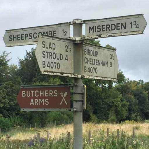 Signpost showing (amongst other places) Miserden to the right, Sheepscombe and the Butcher's Arms to the left.