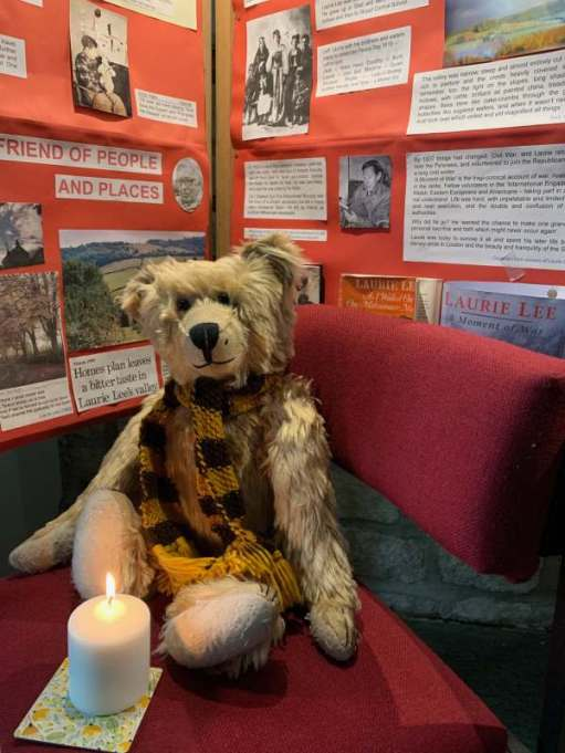 Bertie inside Slad Church sat on a red bench with a candle lit for Diddley.