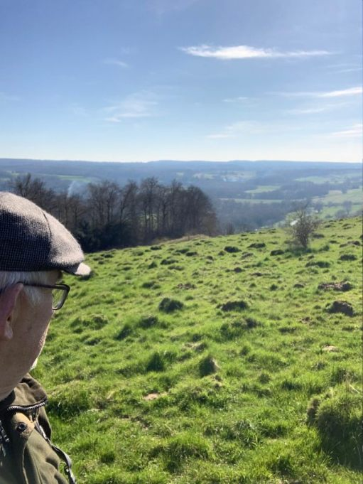Bobby, wearing his cap, looking west to Blackdown across rolling green hills and fields.