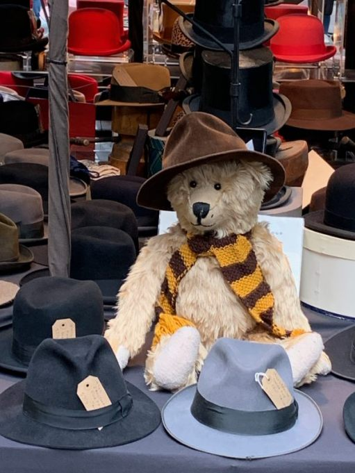Close up of Bertie, wearing his Sutton United scarf and a hat, sat on the vintage hat stall in Spitalsfield Market.