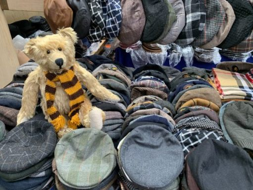 Bertie, wearing his Sutton United scarf, sat amongst the flat caps on the vintage hat stall in Spitalfields Market.